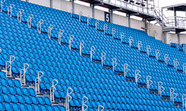 蓝色位子行在体育场内 库存图片