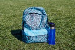 蓝色体育瓶和蓝色体育在绿色体育场盖子挑运 库存图片