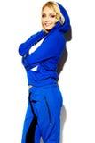 蓝色体育的愉快的甜逗人喜爱的微笑的白肤金发的妇女穿衣 免版税库存照片