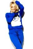 蓝色体育的愉快的甜逗人喜爱的微笑的白肤金发的妇女穿衣 库存照片