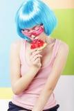 蓝色假发和砰玻璃的时髦妇女吃西瓜的 免版税库存照片