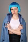 蓝色假发的摆在与横渡的胳膊的女孩和外套 关闭 灰色背景 库存图片