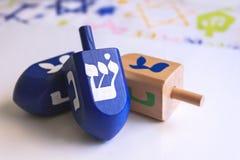 蓝色光明节dreidels有五颜六色的背景 免版税库存照片