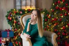 蓝色典雅的晚礼服的年轻美女坐自一个除夕的地板在圣诞树附近和礼物 内部 免版税库存照片