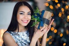 蓝色典雅的晚礼服的年轻美女坐自一个除夕的地板在圣诞树附近和礼物 免版税库存照片