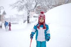 蓝色冬天衣服的,使用逗人喜爱的小男孩室外在雪 免版税库存图片