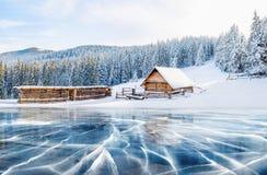 蓝色冰和镇压冰的表面上 冻湖在蓝天下在冬天 在山的客舱 免版税库存照片
