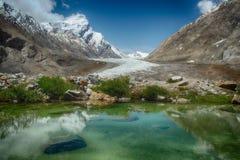 蓝色冰河湖:在水镜子反射与白色云彩、绿色植物沿水的边缘和巨大的mou的明亮的天空 库存图片