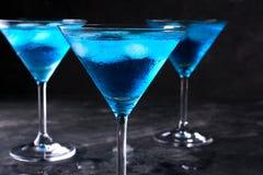 蓝色冷的马蒂尼鸡尾酒鸡尾酒和在玻璃在灰色背景,特写镜头射击的清楚的露滴三块玻璃与冰的 免版税库存图片