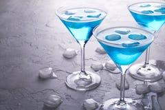 蓝色冷的马蒂尼鸡尾酒鸡尾酒和在玻璃的清楚的露滴三块玻璃与冰的在灰色具体背景 库存照片