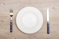 蓝色刀子和叉子与白色板材 库存照片