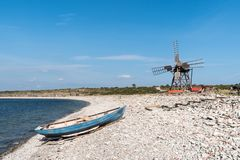 蓝色划艇和一台老风车由海边 库存图片