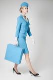 蓝色制服和手提箱的迷人的空中小姐在灰色 库存照片