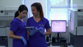 蓝色制服的谈论画象两专业女性的试验室工怍人员站立在计算机前面的研究 股票录像