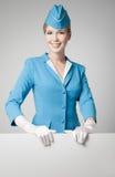 蓝色制服的迷人的空中小姐有在G的空白表格的 库存图片