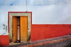 蓝色前房子老红色墙壁 库存图片