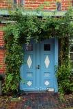 蓝色前门在有上升的植物的一个历史的房子里的 免版税库存照片