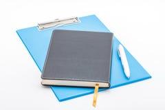 蓝色剪贴板、笔记本和笔 免版税库存照片
