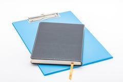 蓝色剪贴板和笔记本 免版税库存图片