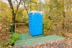 蓝色化工洗手间在森林 库存图片