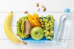 蓝色午餐盒用小学生的健康食物有瓶的在白色木背景的水 免版税库存图片