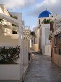 蓝色半球形的教会在这条街道背景中在Oia在圣托里尼,希腊 免版税库存图片