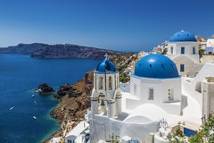 蓝色半球形的教会在Oia,圣托里尼锡拉,基克拉泽斯海岛,爱琴海村庄, 免版税库存图片