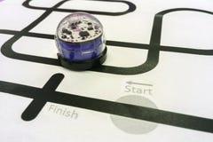 蓝色发光的塑料象编程的金属机器人汽车跑在白皮书黑线  免版税库存图片