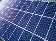 蓝色发光的太阳在大厦屋顶的照片流电盘区系统特写镜头表面  可更新的生态绿色发电 免版税库存图片