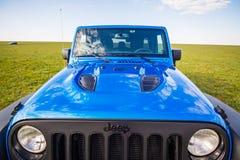蓝色吉普争吵者Rubicon无限在狂放的郁金香领域在盐水水库湖Manych-Gudilo附近 免版税图库摄影