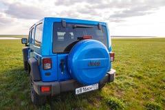 蓝色吉普争吵者Rubicon无限在狂放的郁金香领域在盐水水库湖Manych-Gudilo附近 图库摄影