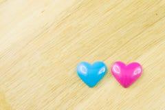 蓝色和桃红色心脏,木背景 免版税库存照片