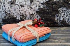 蓝色和桃红色棉花毛巾栓与透雕细工辫子和装饰美丽的花束以白桦树皮为背景 库存图片