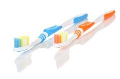 蓝色和橙色牙刷 免版税库存照片