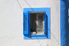 蓝色和白色关闭了在墙壁的窗口在希腊海岛上 免版税库存照片