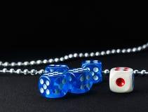 蓝色和白色切成小方块和在黑暗的背景的金属链子 图库摄影