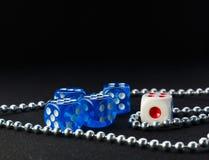 蓝色和白色切成小方块和在黑暗的背景的金属链子 免版税库存图片