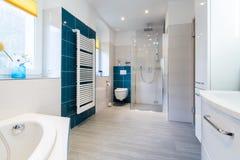蓝色和白色口气的宽敞卫生间与激昂的地板、未经预约而来的阵雨、水槽虚荣和天窗 库存照片