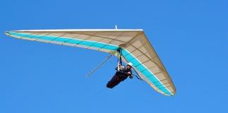 蓝色和白色悬挂式滑翔机有蓝天背景 库存照片