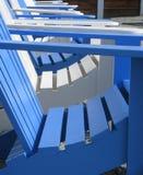 蓝色和白色木adirondack椅子 免版税图库摄影
