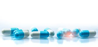 蓝色和白色胶囊药片在与阴影的白色背景传播了并且复制空间 全球性医疗保健概念 抗菌药 库存照片