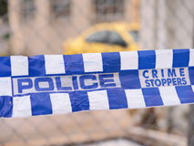 蓝色和白色警察把封锁与一辆黄色汽车在一个工业区,澳大利亚的一个区域录音2016年 免版税库存图片