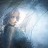 蓝色和红色丝绸衣裳的一名年轻红头发人妇女 图库摄影