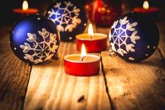 蓝色和红色圣诞节球和红色点燃了在木背景的蜡烛 免版税库存图片