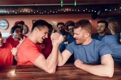 蓝色和红色队在娱乐酒吧在背景中扇动武器角力与爱好者 免版税库存照片
