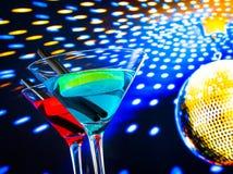 蓝色和红色鸡尾酒有与空间的金黄闪耀的迪斯科球背景文本的 免版税库存照片