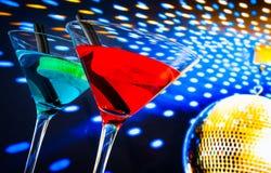 蓝色和红色鸡尾酒有与空间的金黄闪耀的迪斯科球背景文本的 免版税图库摄影