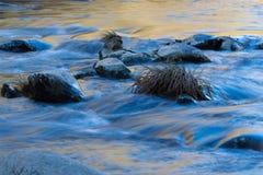 蓝色和金与天空和秋叶的水反射的岩石摘要 免版税库存图片