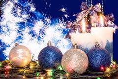 蓝色和银色圣诞节球、一本发光的诗歌选和两个灼烧的蜡烛在欢乐烟花的背景 免版税库存图片