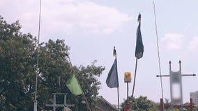 蓝色和黄旗由风挥动反对绿色树 股票视频